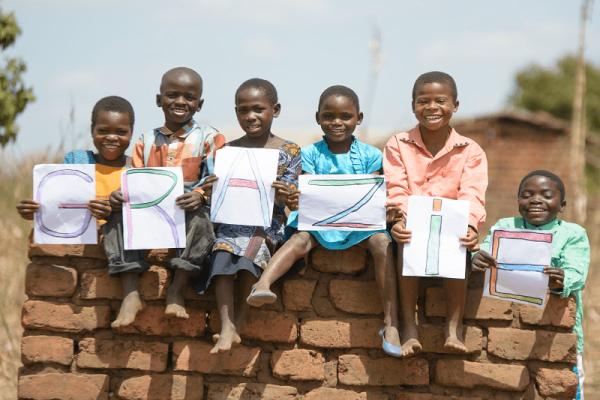 6 bambini del Malawi su un muretto tengono le lettere per formare la parola grazie