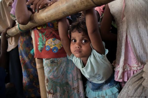 Bambina Rohingya mezzo busto guarda in camera. Immagine molto colorata.