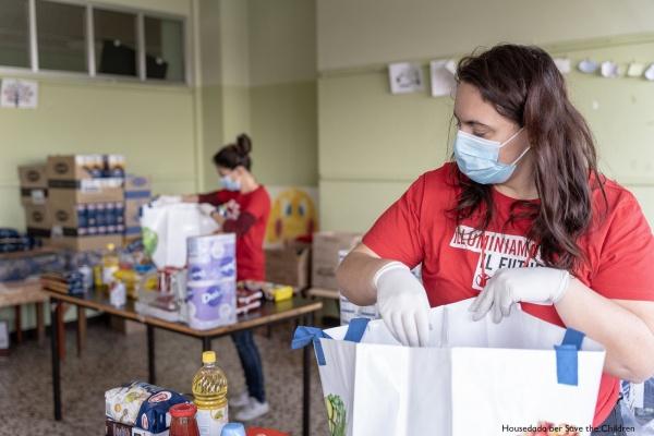 due operatrici save the children con mascherina mentre preparano pacchi alimentari per le famiglie bisognose