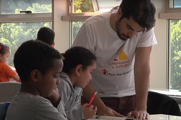 operatore di un punto luce aiuta due bambini a fare i compiti