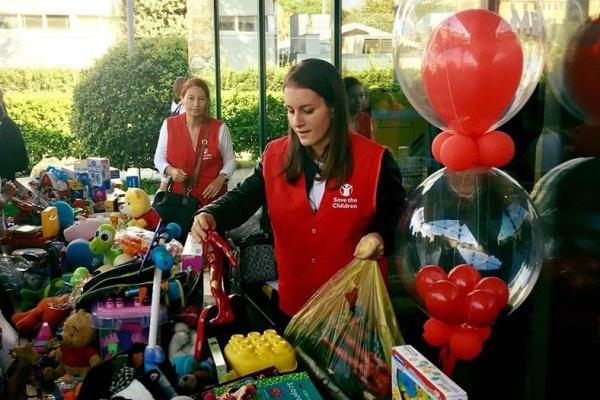 due volontarie di save the children davanti a un banco con tanti giochi per raccogliere fondi per i bambini