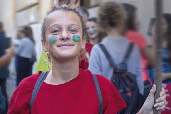 bambina con maglietta rossa tiene un cartello durante lo sciopero per il clima a Roma