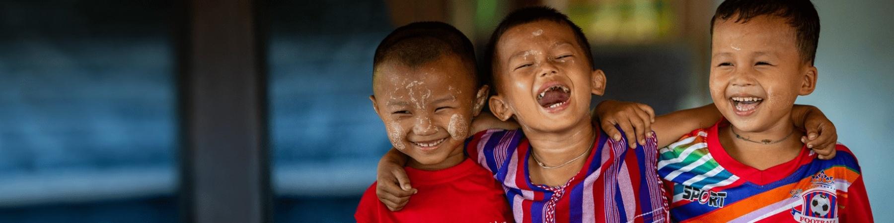 3 bambini sorridenti che si abbracciano
