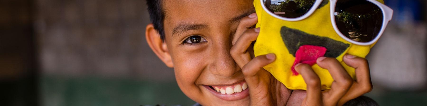 bambino sorridente in primo piano con una maschera gialla davanti a metà volto