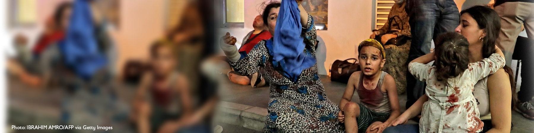 persone sedute a terra ferite tra cui due bambini feriti e una donna velata di blu con un braccio fasciato Libano