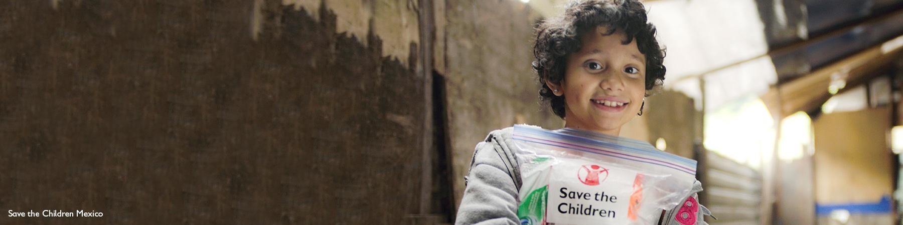 bambino messicano con in mano un kit igienico per la prevenzione coronavirus
