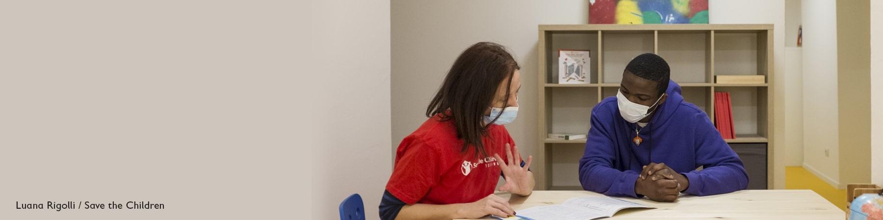 seduti a un tavolo, indossando le mascherine, un operatrice di Save the Children con maglietta rossa e un ragazzo con maglioncino blu guardano insieme degli esercizi su un foglio