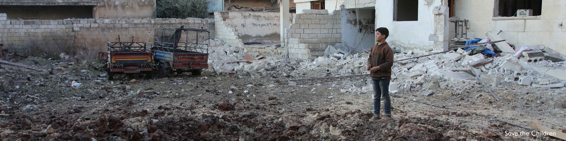 bambino in piedi in mezzo alle macerie provocate da un bombardamento in Siria ad Idlib