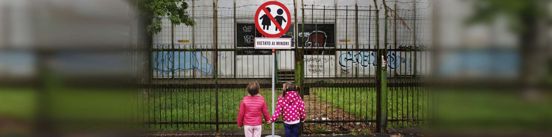 due bambine per mano davanti a un cartello con scritto vietato ai minori