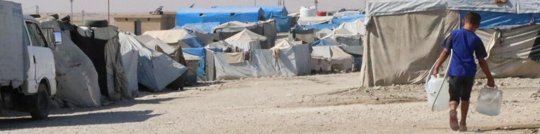 bambino nel campo rifugiati con due taniche