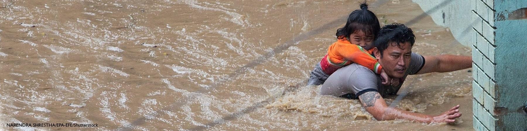 papà con la figlia sulle spalle cerca di uscire da un fiume creatosi dopo l inondazione