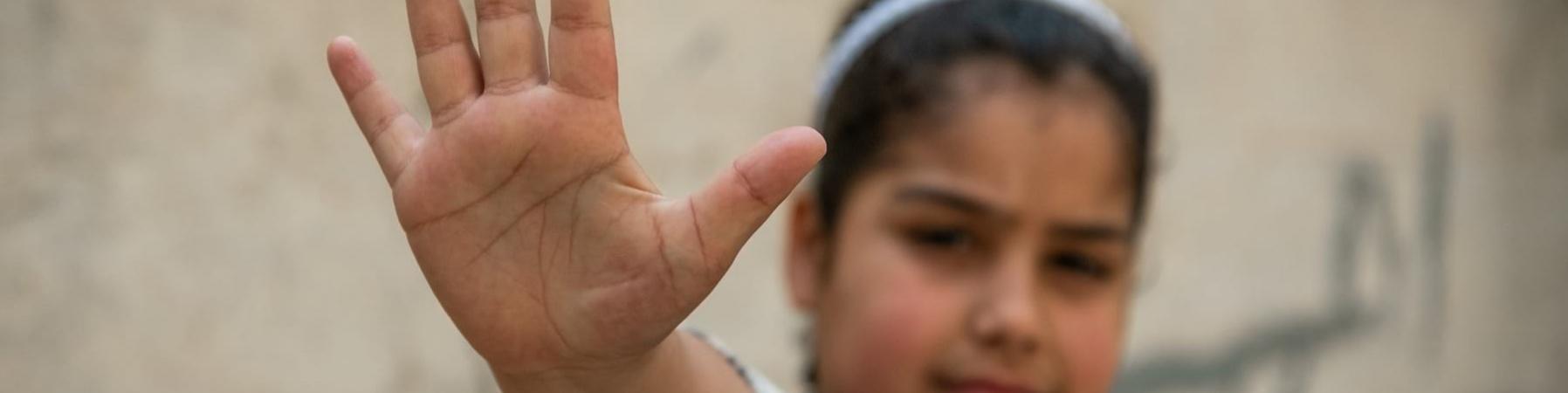 Primo piano di una bambina con la mano davanti facendo gesto di stop