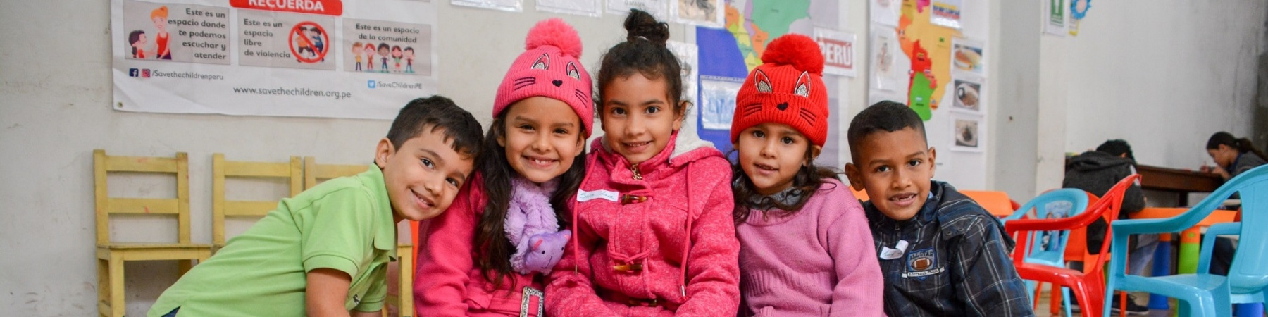 5 bambini seduti per terra a giocare in un asilo. Indossano maglioncini colorati