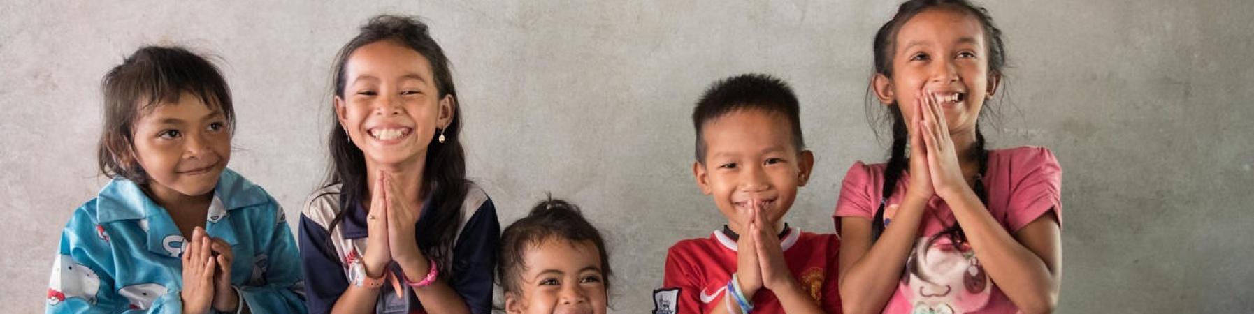5 bambini cambogiane in piedi con le mani giunte sorridono