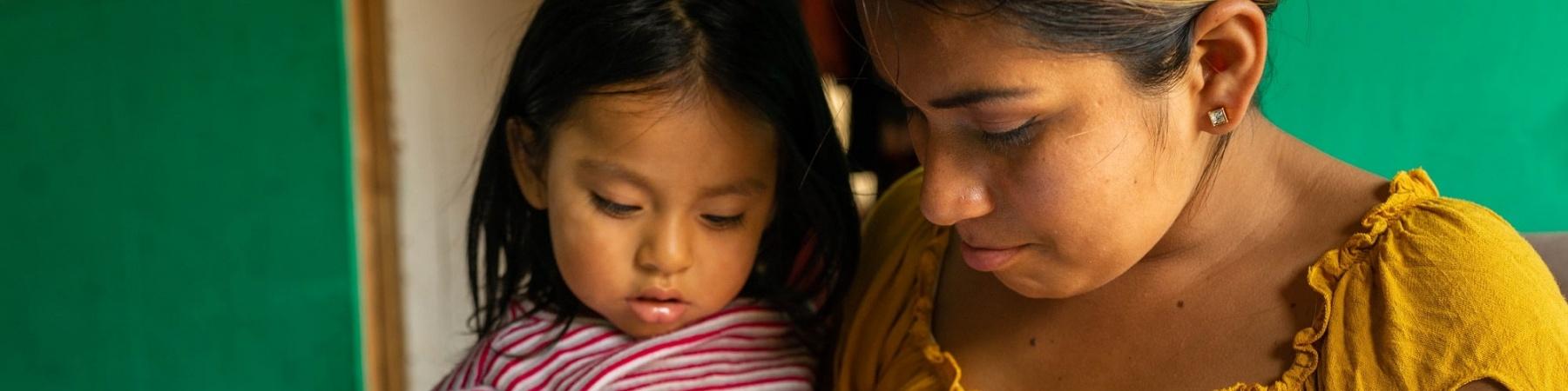bimba in braccio alla madre mentre colorano insieme un libro da colorare per bambini