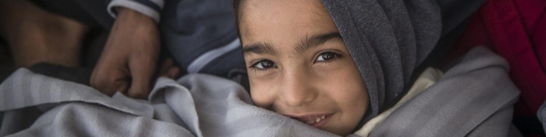 Un bambino con cappuccio grigio in testa sorride avvolto in una coperta anche essa grigia.