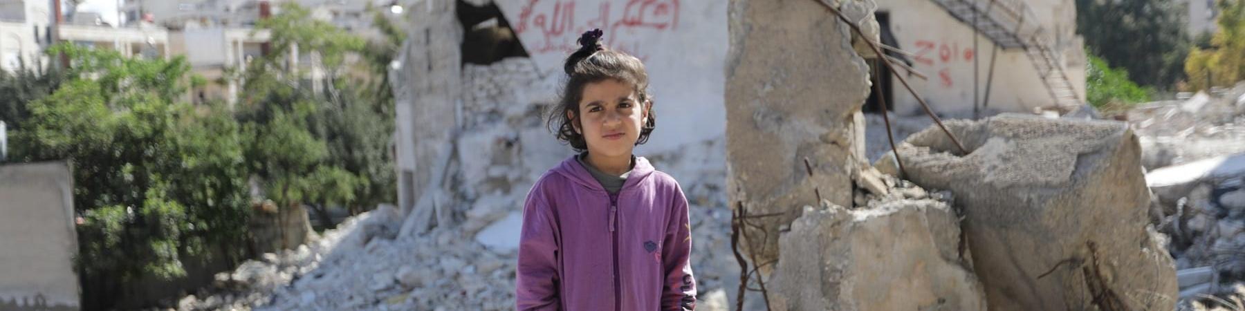 Bambina siriana in piedi tra le macerie. Indossa pantaloni neri e una felpa viola e tiene le mani nelle tasche
