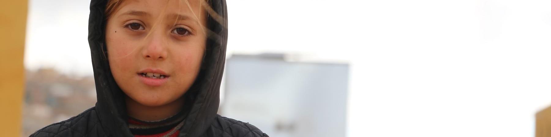Mezzo busto di una bambina siriana bionda con una giacca nera e il cappuccio in testa.