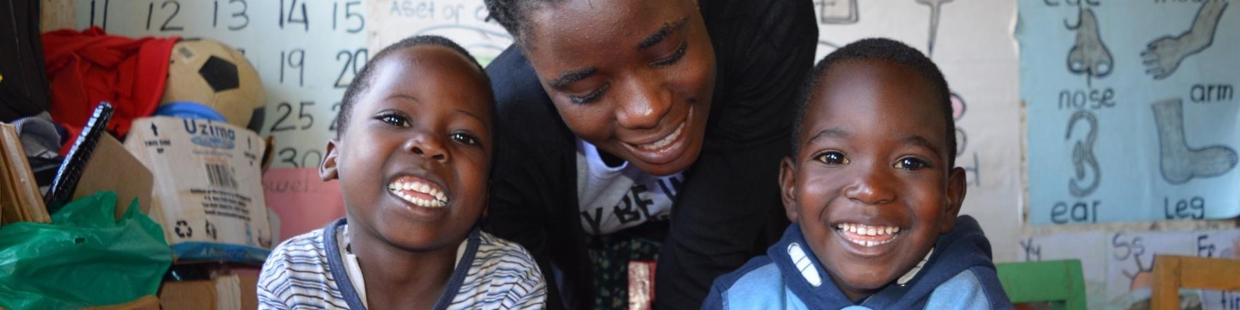 2 bimbi neri con la maestra studiano sorridenti seduti al banco di scuola