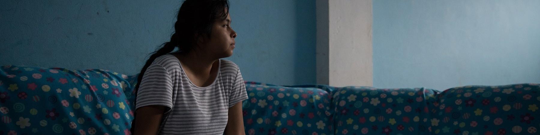 Ragazza in penombra di profilo seduta su un divano