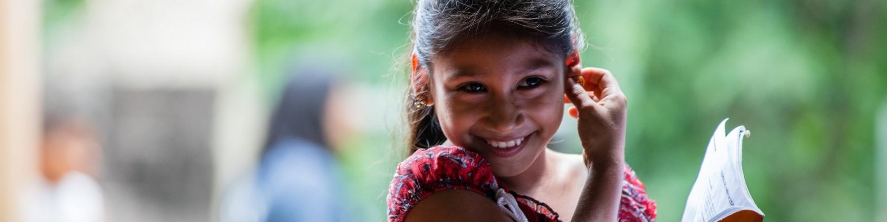 bambina di el Salvador sorridente con una borsa a tracolla e un libro in mano