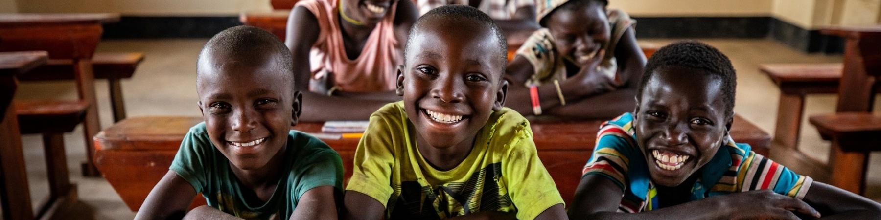 una classe di bambini seduta ai banchi di scuola in Africa, Uganda