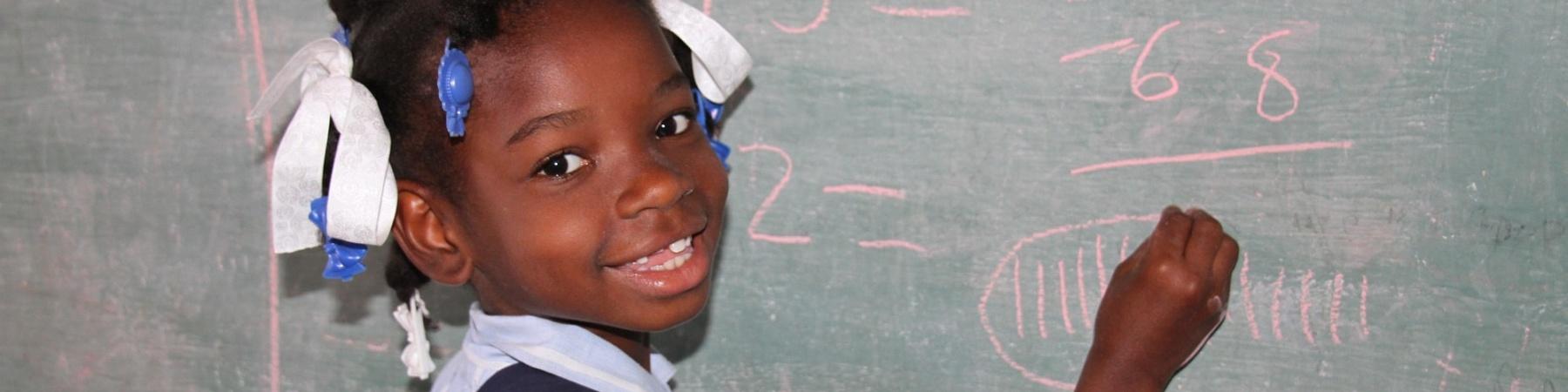 bimba nera di Haiti che scrive alla lavagna a scuola e ci guarda con un grande sorriso. Vestita con una camicia azzurra ha un nastro tra i capelli pettinati con due treccine.
