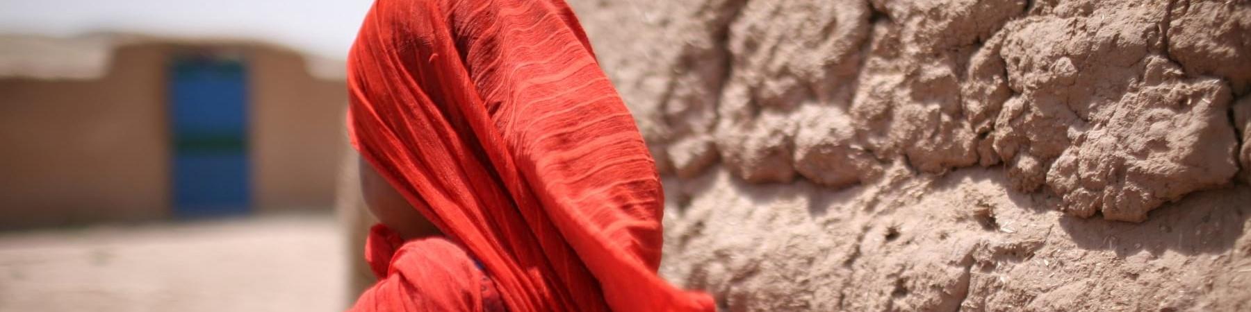 Bambina afghana di spalle con foulard rosso
