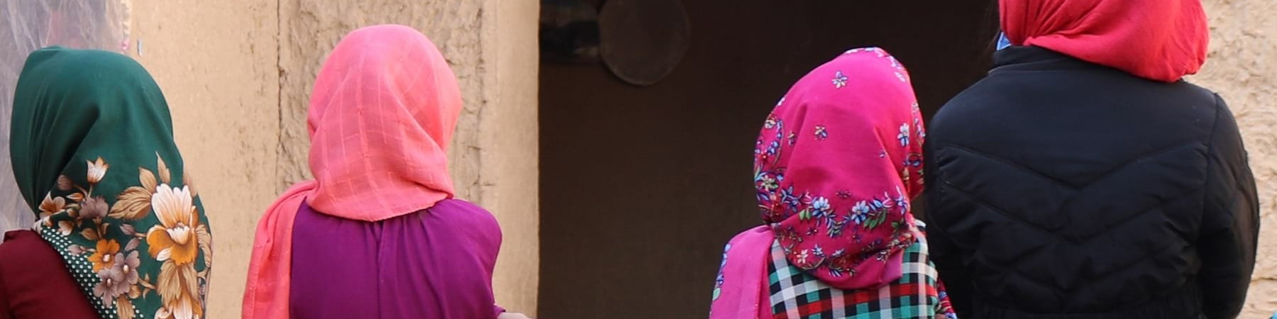4 bambine afghane di spalle si tengono per mano, indossano chador e vestiti colorati