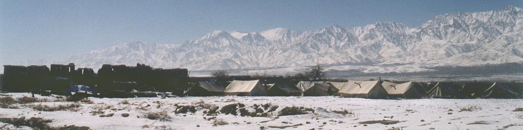 tende di un campo profughi su un campo di neve ai piedi di alte montagne innevate in afghanistan