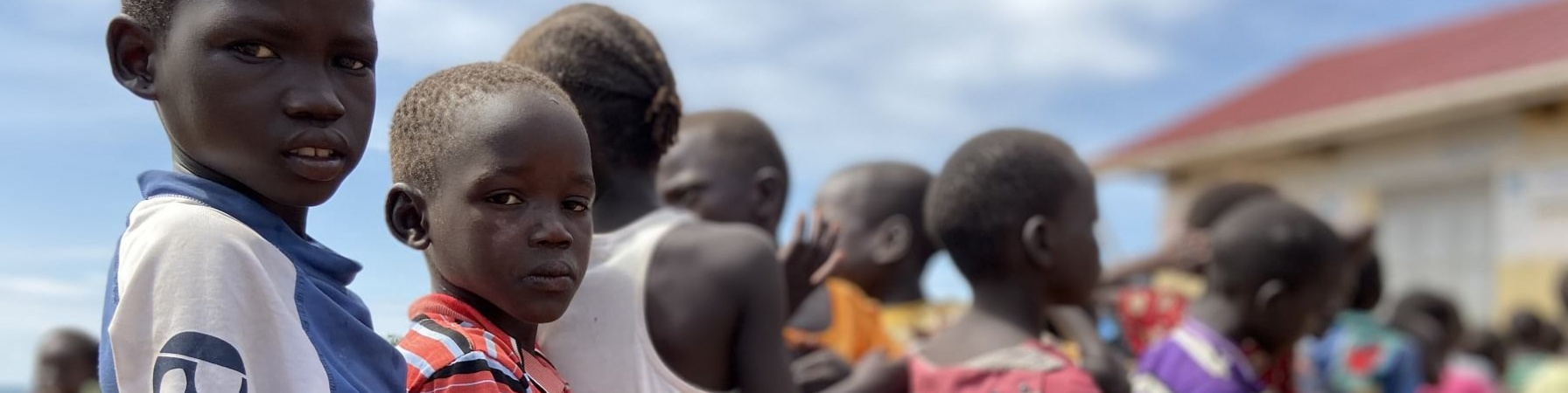 Bambini ugandesi in fila uno dietro l altro all aperto