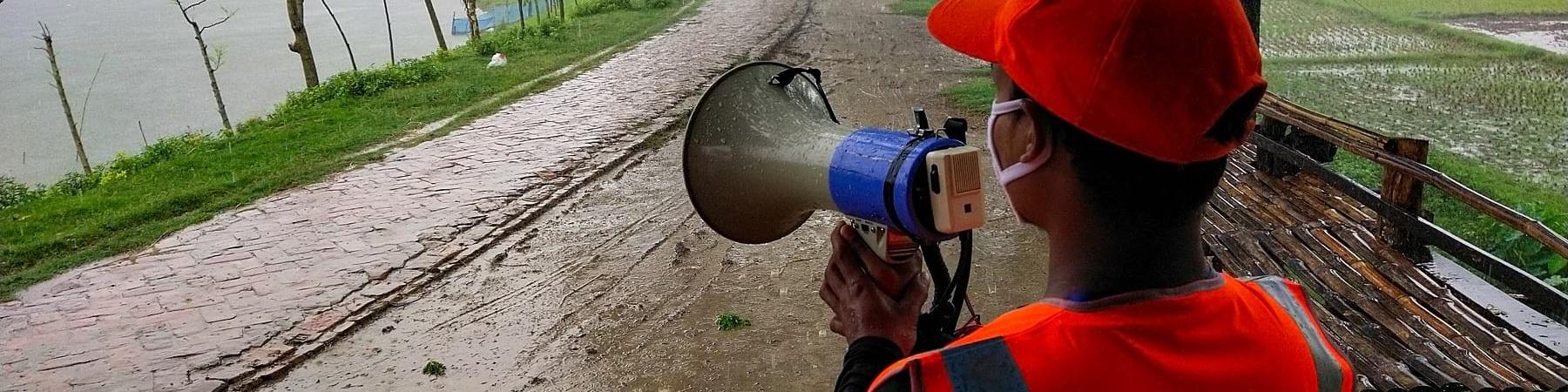 Operatore di spalle con megafono in mano