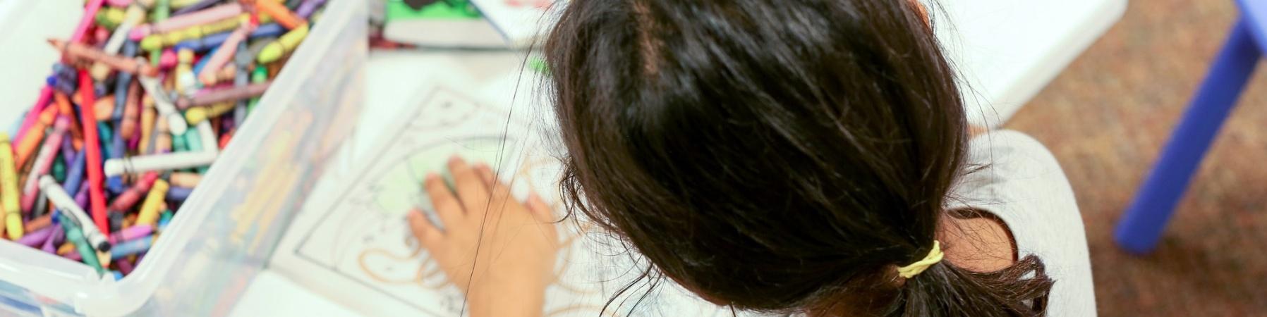 bambina ad un tavolo che colora e disegna