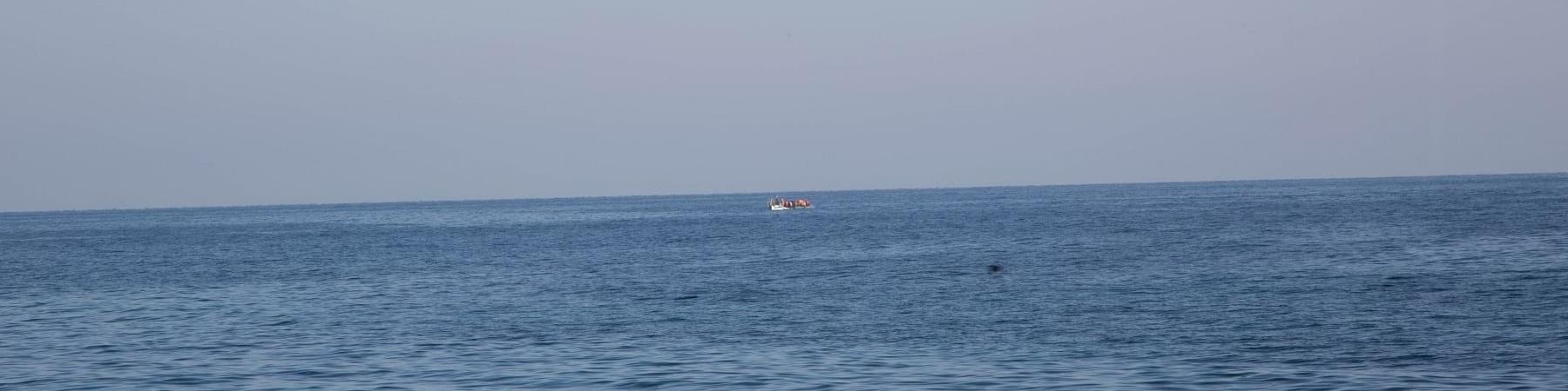 orizzonte tra cielo e mare, in lontananza una piccola imbarcazione
