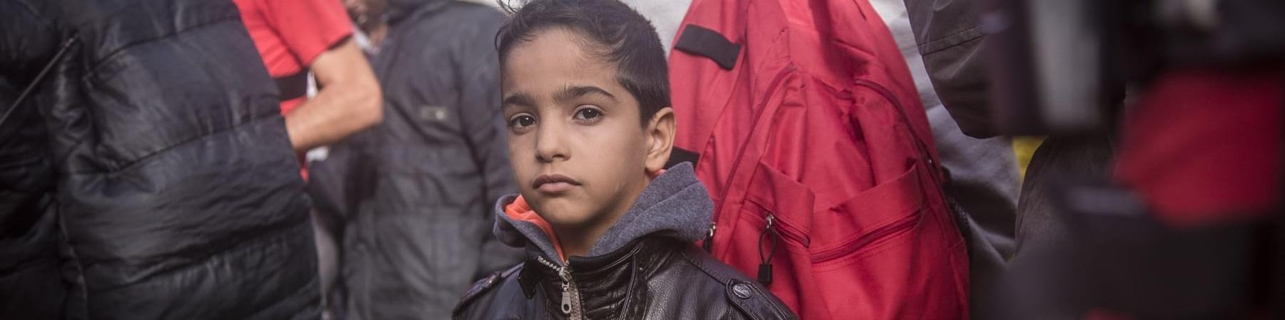 Un bambino in mezzo a tante persone guarda in camera. Indossa una giacca di pelle nera con la zip. Lui è moro e ha i capelli corti