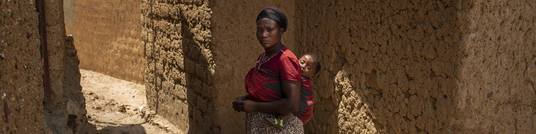Donna ruandese in piedi tra due mura porta sulle spalle un bambino neonato nella fascia. Lei indossa una maglia rosa e una lunga gonna marrone.