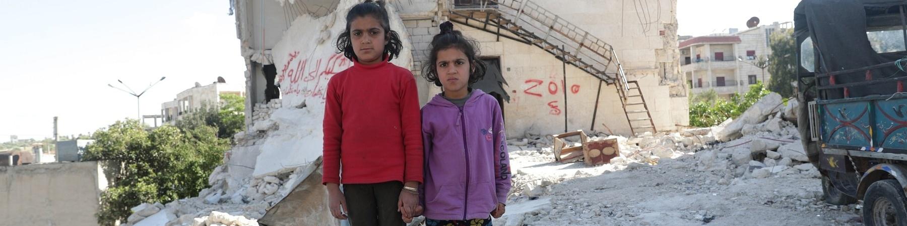 Due bambine siriane in piedi tra le macerie
