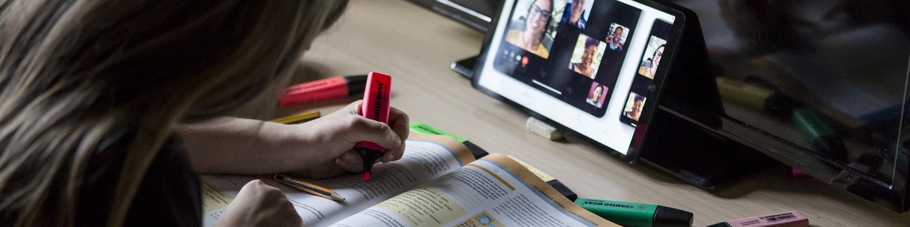 Bambina di spalle evidenzia libro scolastica mentre fa lezione a distanza su un tablet davanti a lei