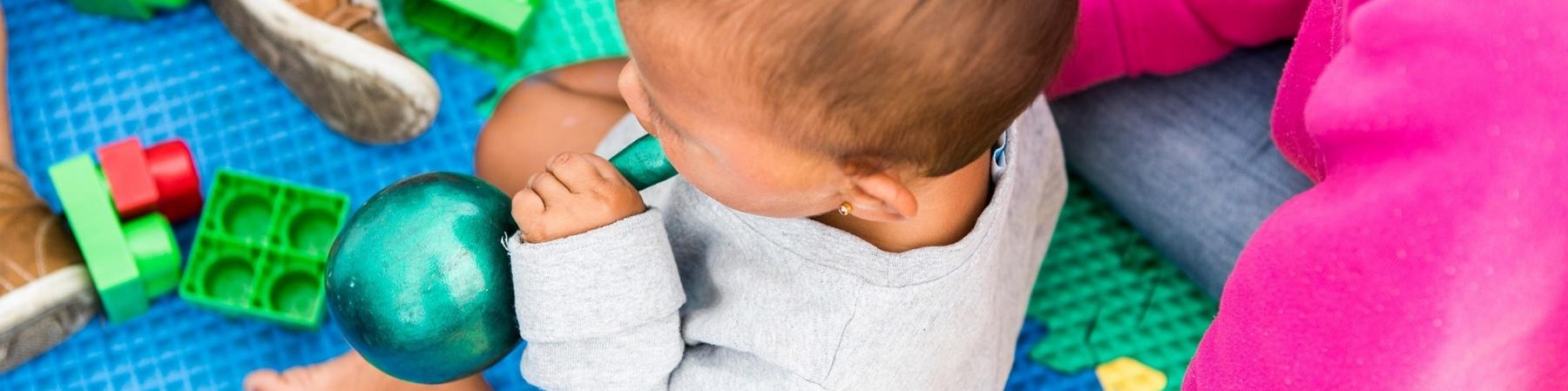 bimbo seduto su un tappeto colorato di gomma che gioca insieme alla sua mamma