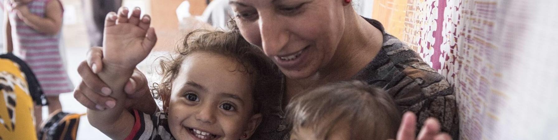 Una mamma abbraccia e guarda due bambini piccoli sorridenti