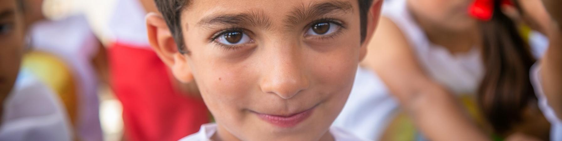 Primo piano di un bambino che guarda in camera con camicia bianca