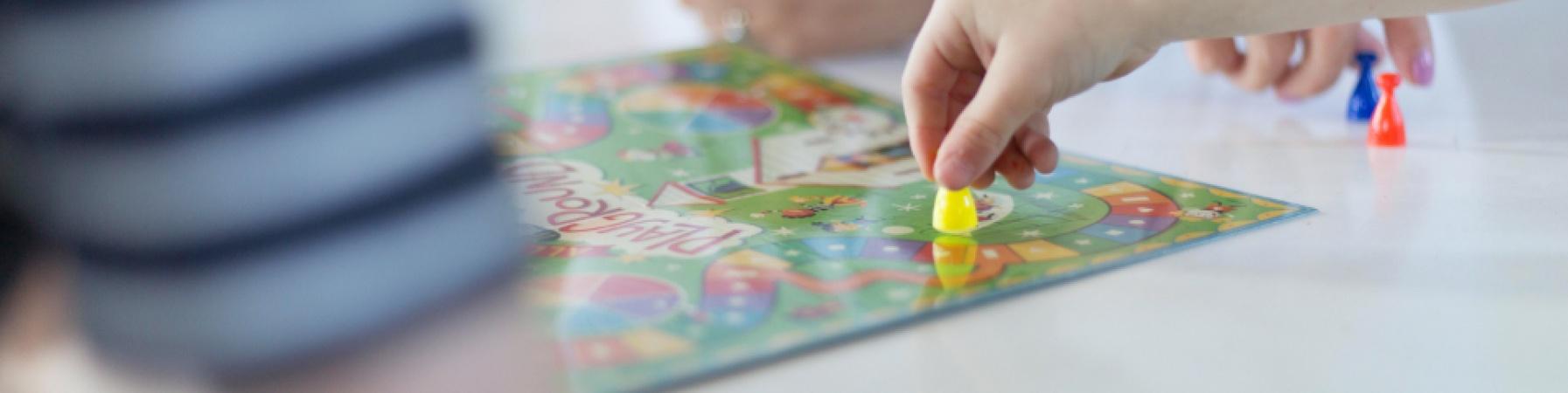 primo piano gioco da tavolo con mani dei bambini che spostano pedine