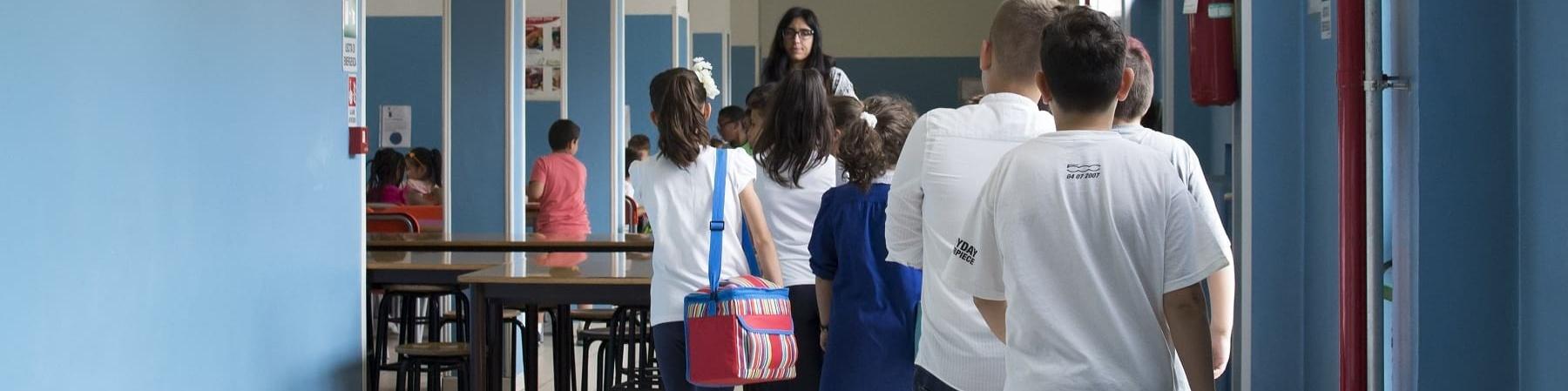 Bambini in fila nel corridoio di una scuola sono inquadrati di spalle mentre camminano verso l insegnate sullo sfondo girata verso di loro
