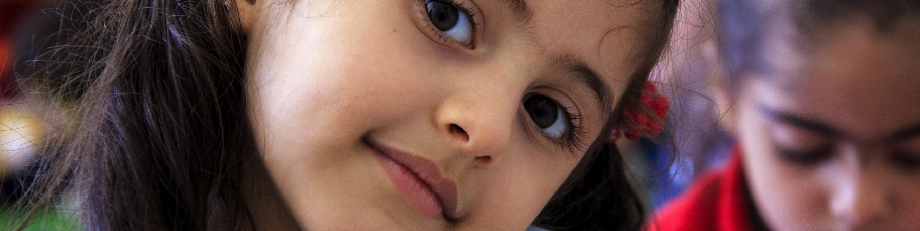 Primo piano bambina mora testa inclinata