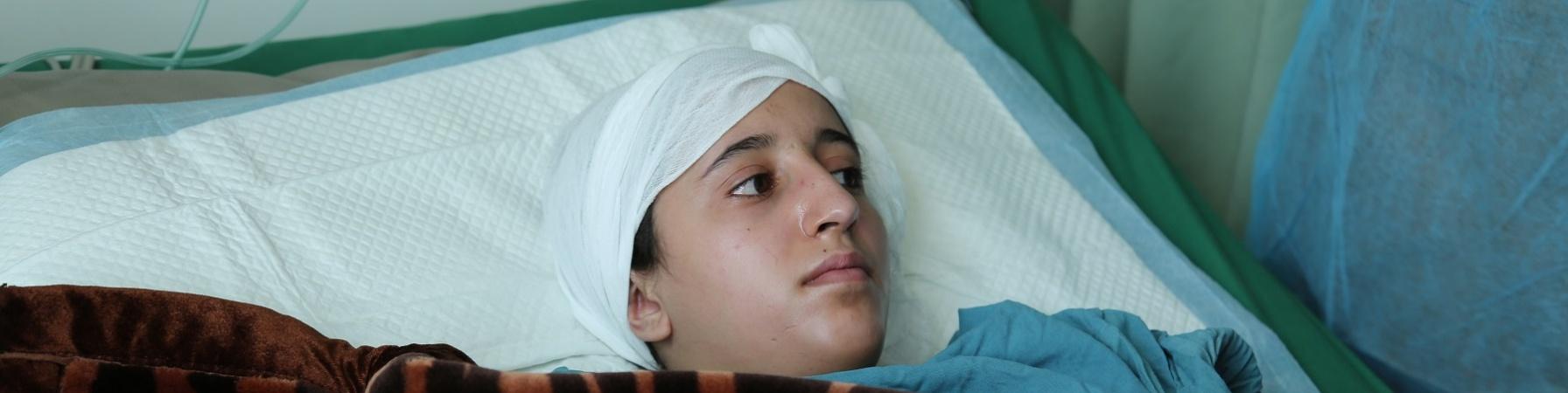 Adolescente yemenita in letto di ospedale con fasciatura alla testa