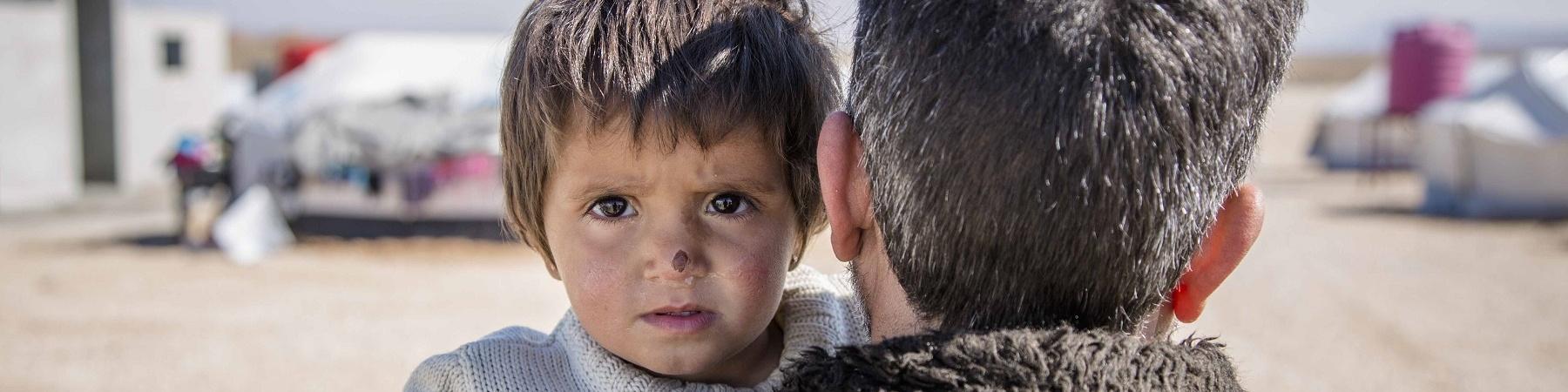 bambina siriana in braccio al papà di spalle