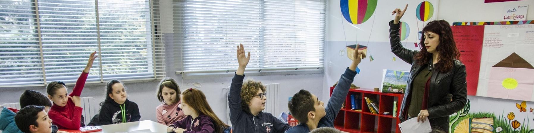 bambini in classe con maestra che alzano la mano