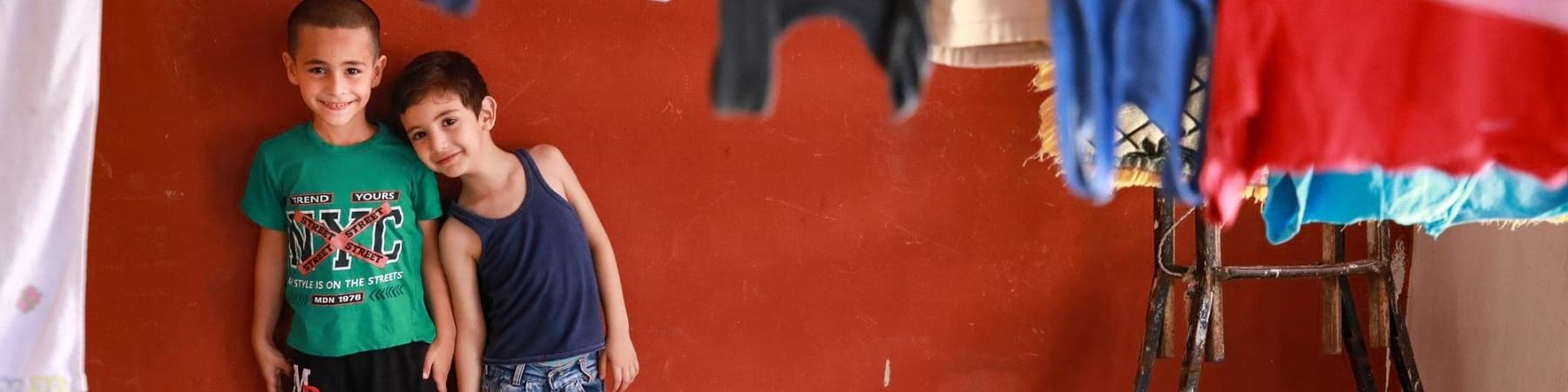 due bambini ripresi in lontananza all interno di una stanza con le pareti rosse sono appoggiati al muro uno a fianco dell altro. davanti a loro i panni stesi.