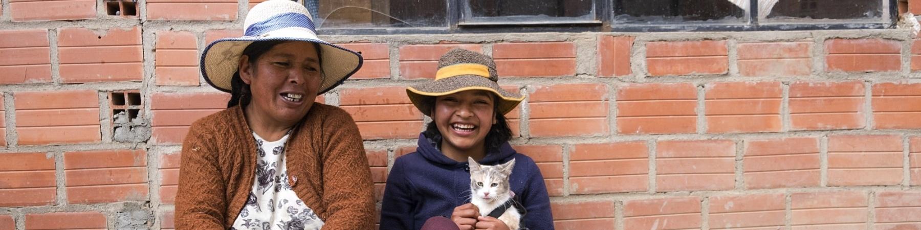 Donna e bambina in Bolivia sedute per terra, sorridenti