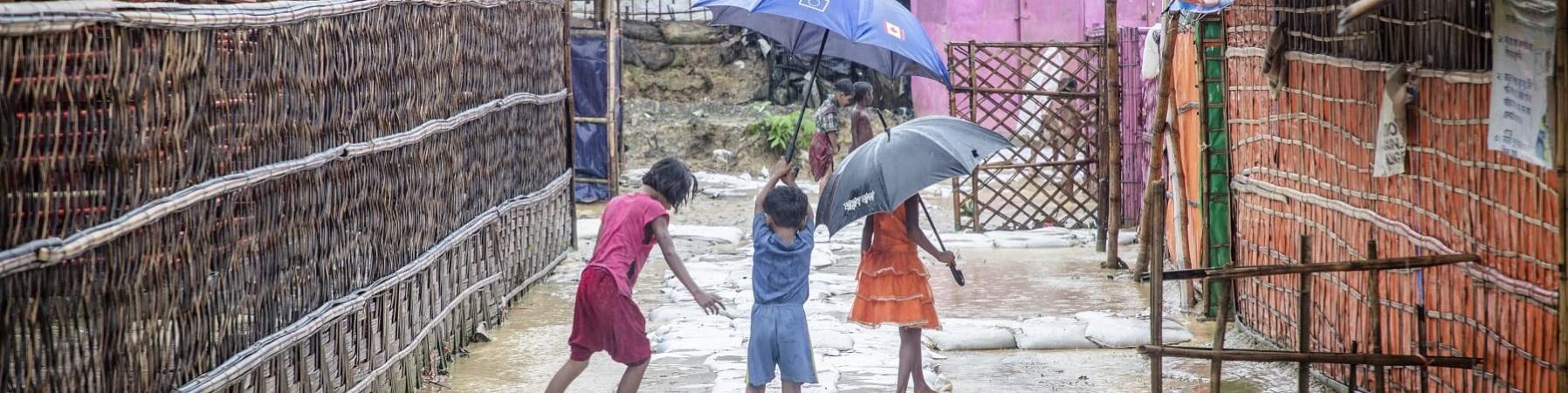 Tre bambini di spalle reggono ombrello e giocano in uno slum allagata del Bangladesh
